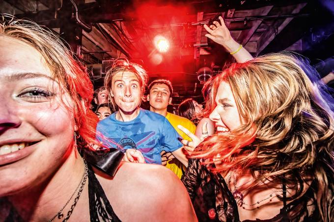 Revelers jump around in the mosh pit during a night out at