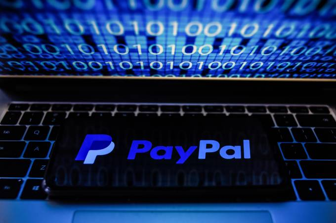 In this photo illustration a PayPal logo seen displayed on a