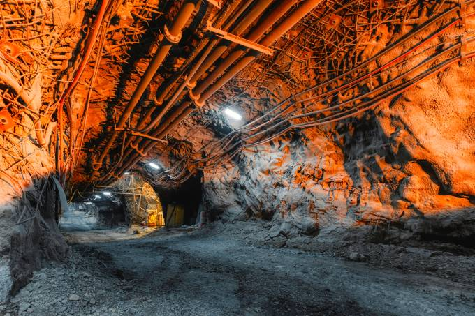 Tunnel of the mining of an underground mine. Lots of pipelines on the ceiling and rail track for trolleys
