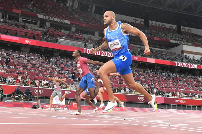 Italy's Lamont Marcell Jacobs celebrates as he crosses the finish line in the men's 100m final during the Tokyo 2020 Olympic Games at the Olympic Stadium in Tokyo on August 1, 2021. (Photo by Jewel SAMAD / AFP)