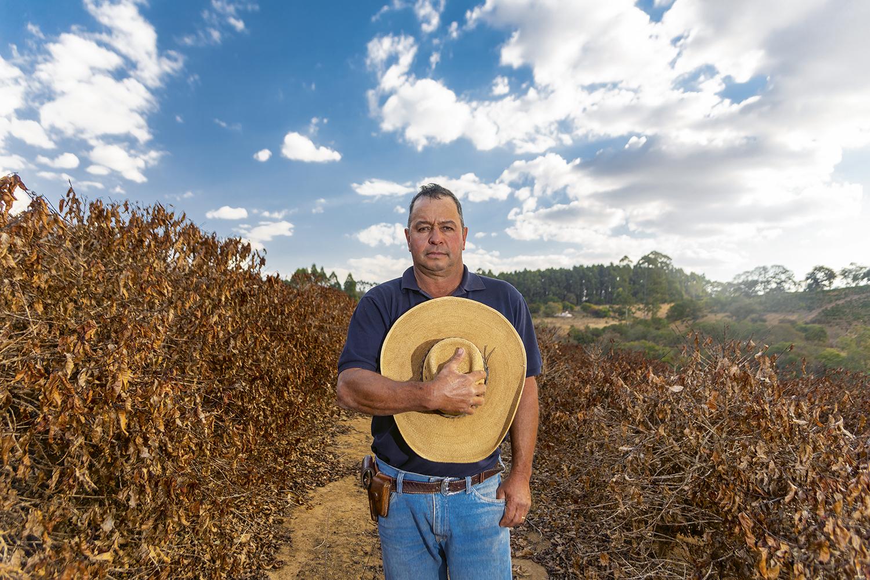 """RECALCULANDO - Em um ano em que a expectativa era de recorde na colheita, a chuva não veio, e os donos de cafezais do cerrado mineiro refizeram as contas. Cícero Souza, 56 anos, perdeu 300000 do 1 milhão de pés que mantém na região de Jacuí. Com isso, talvez não consiga dar conta das sacas para exportação. """"Espero não ter de vender um pedaço da terra. Isso aqui é minha vida"""". -"""
