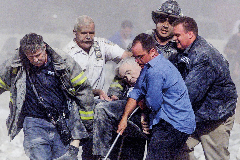 SIMBÓLICO- Capelão dos bombeiros carregado por amigos: a vítima número 1