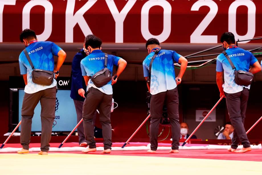 Voluntários limpam o chão antes das competições de judô na Nippon Budokan Arena -