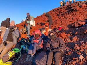 Tadashi, Erica, Max e Nina no topo do Monte Fuji, acompanhando o amanhecer -