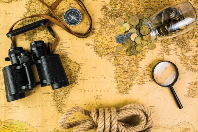 travelling-equipments-and-glass-jar-with-coins-on-vintage-map