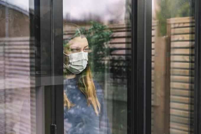 Teenage girl looking through window with mask