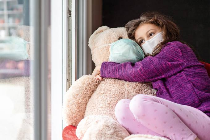Cute little girl whit protective mask standing next to the window with her teddy bear