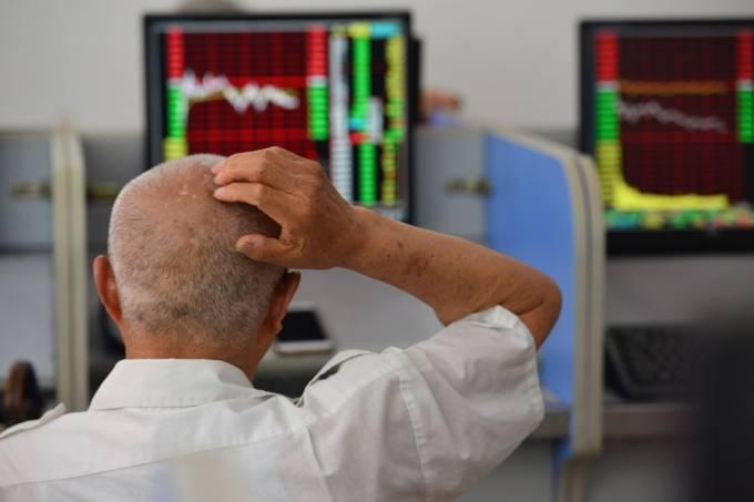An elderly stockholder looks at the stock market data on a