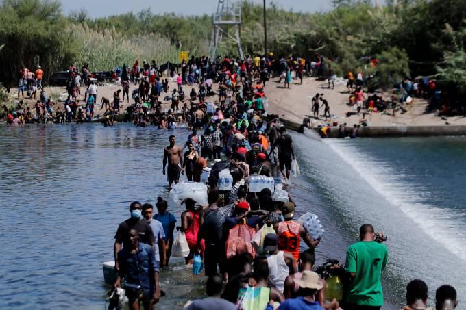 Imigrantes cruzam a fronteira do México com os Estados Unidos neste sábado (18)