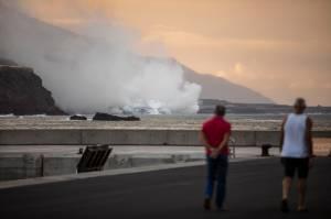 La gente observa una nube de humo formada por el contacto de la lava del volcán Cumbre Vieja con el océano en La Palma - 29/09/2021