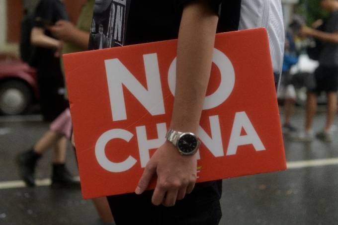 """A man carrying a sign saying """"No China"""" while taking part on a march in Taipei downtown"""