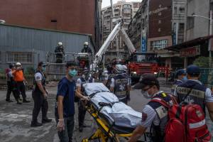 KAOHSIUNG, TAIWAN - OCTOBER 14: Paramedics transport a dead body from a residential building in the wake of a fire on October 14, 2021 in Kaohsiung, Taiwan. Additional deaths are feared as at least 14 were confirmed dead after a residential building fire in the southern Taiwanese city, United Daily News reported. (Photo by Lam Yik Fei/Getty Images)
