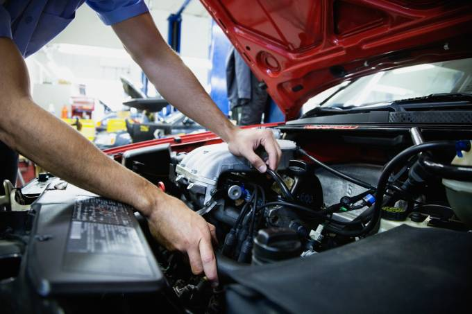 Close up of male auto mechanic working on engine in auto repair shop