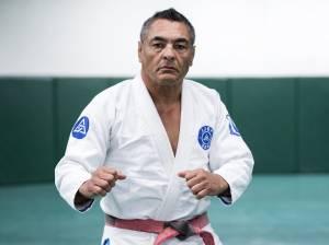 A imagem mostra Rickson Gracie de quimono, no tatame
